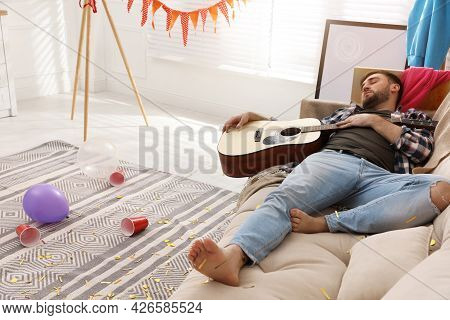 Young Man With Guitar Sleeping On Sofa In Messy Room After Party