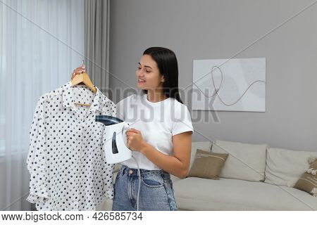 Woman Steaming Blouse On Hanger At Home. Space For Text