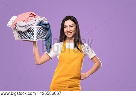 Optimistic Young Housewife In Yellow Apron Carrying Basket With Colorful Cloth For Laundry During Ho