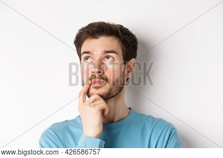 Face Of Young Caucasian Man Looking Up Pensive, Making Choice Or Thinking, Pondering While Standing