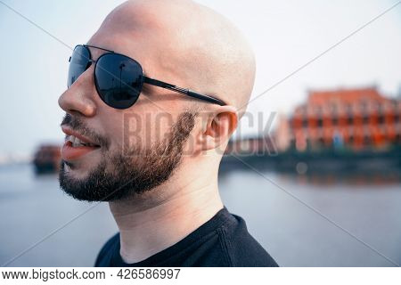 Happy Young Man In Sunglasses Strolling Along A River And Daydreaming. Bald Bearded Masculine Guy Sm