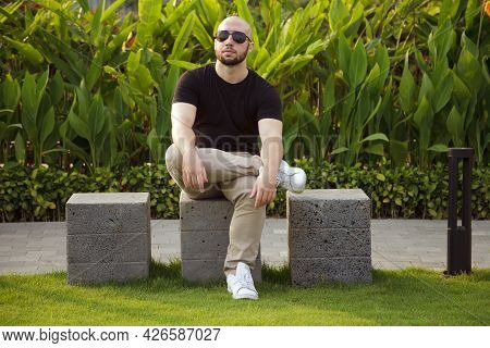 Young Bearded White Man In Sunglasses And A Black T-shirt Sitting On A Bench In A Park. Bald Ripped
