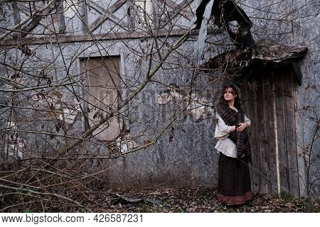 A Woman Dressed In Vintage Clothes Stands Tall At An Old Wooden Door Made Of Boards. A Woman At An O