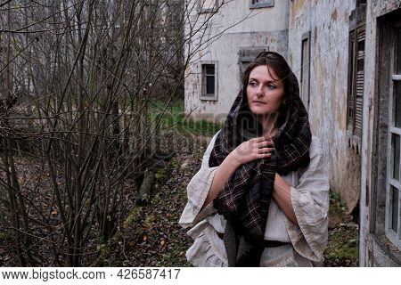 The Woman Wrapped Herself In A Shawl Against The Autumn Landscape Of The Old European City. Sad Mela