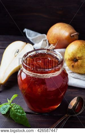 Homemade Pear Jam In A Jar And Fresh Pears On A Wooden Background.