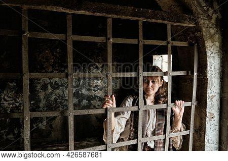 A Young Woman Stands Behind The Bars Of An Ancient Prison Cell. Criminal Woman In Vintage Clothes, W