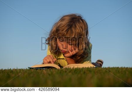 Child Boy Is Reading A Book On The Spring Park. Relaxing On The Grass In The Garden. Outdoor Educati