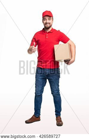 Content Bearded Delivery Male In Red Uniform Standing With Carton Box And Showing Thumb Up Sign On W