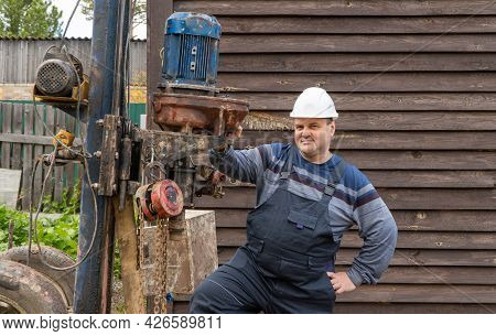 Man Stands Near A Drilling Rig. Drilling Wells For Drinking Water. Development Of Soil For The Organ