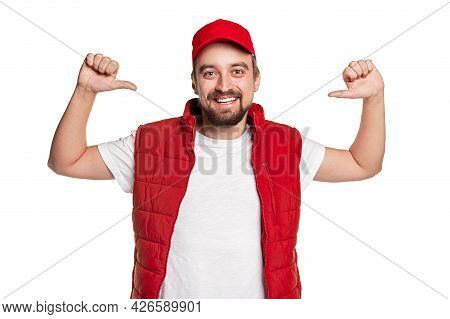 Cheerful Cool Confident Bearded Male Courier In Red Uniform Pointing At Himself With Thumbs Against