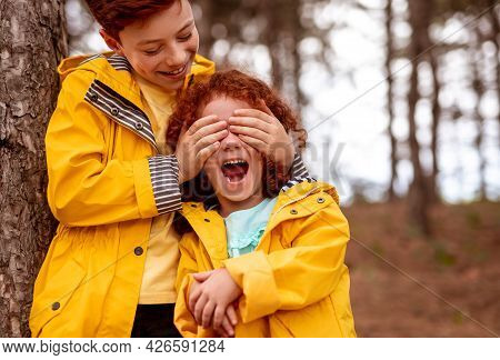 Cheerful Redhead Boy Covering Eyes Of Excited Little Sister Wearing Similar Yellow Raincoat While Ha