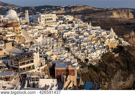 Fira, Santorini, Greece - June 27, 2021: The Whitewashed Town Of Fira In Warm Rays Of Sunset On Sant