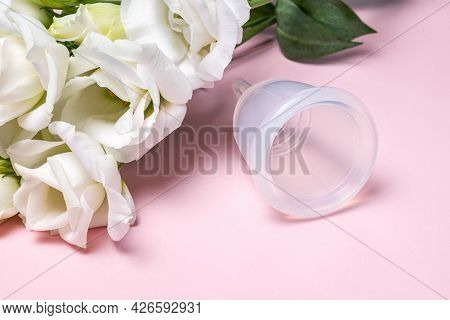 Reusable Menstrual Cup And Bouquet Of Tender White Eustoma Flowers On Pink Background. Women Health