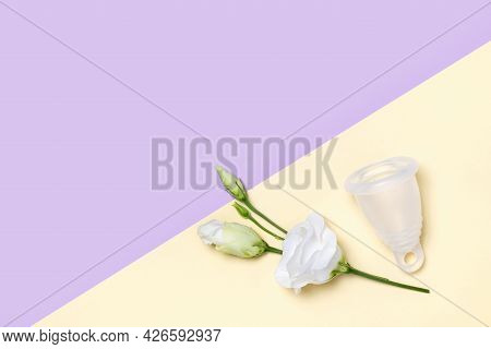 Reusable Menstrual Cup And Tender White Flower Eustoma On Pastel Yellow And Purple Background. Women