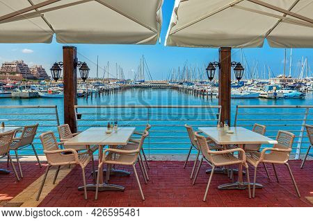 White tables and chairs under umbrellas in outdoor restaurant overlooking small port with yachts in Ashqelon - city on Mediterranean sea in Israel.