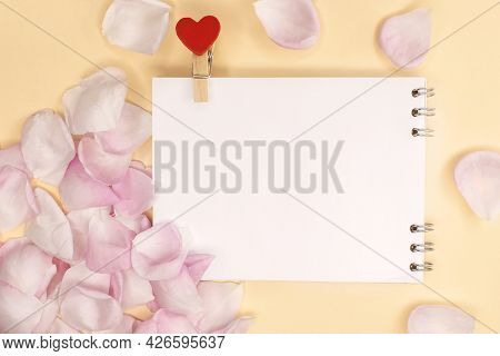 An Open Empty Notebook With A Clothespin In The Shape Of A Heart Among Pink Rose Petals. Festive Bac