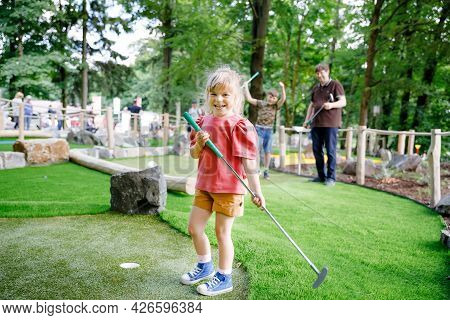 Cute Preschool Girl Playing Mini Golf With Family. Happy Toddler Child Having Fun With Outdoor Activ