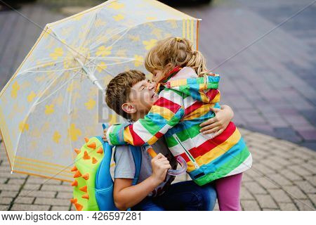 School Kid Boy Picks Up The Little Sister, Preschool Girl From Kindergarten. Two Happy Children With