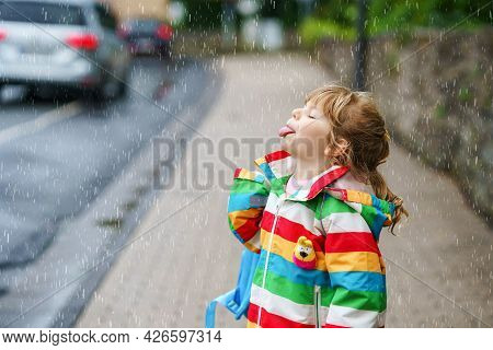 Portrait Of Little Toddler Girl On Rainy Day. Happy Positive Child Running Through Rain, Puddles. Pr