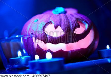 Halloween pumpkin and candles on table