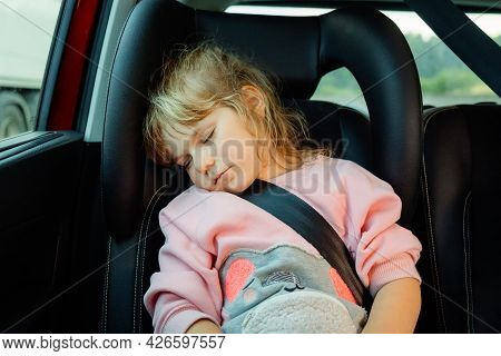 Portrait Of Cute White Preschool Girl Sleeping In Car During Family Trip. Child Sitting In Car Seat.