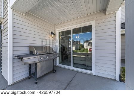 Exterior Of A House With A Sliding Glass Door And Vinyl Sidings