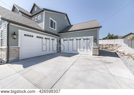 Exterior Of A House With Concrete Driveway And Two Closed White Garage Doors With Windows