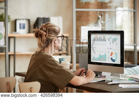 Rear View Of Young Businesswoman Sitting At The Table In Front Of Computer Monitor And Working With