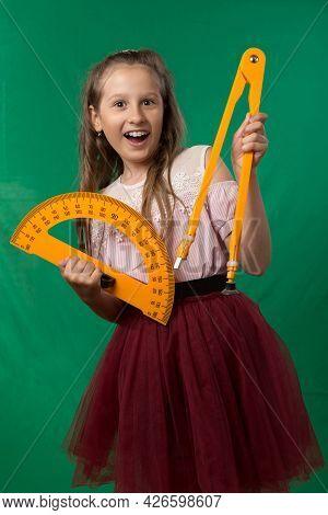 Little Cute Schoolgirl Posing On A Green Background. Studio Photo Of A School Theme.