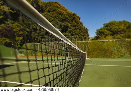 General view of tennis court and tennis net on sunny day. retreat, leisure time facilities and active lifestyle concept.