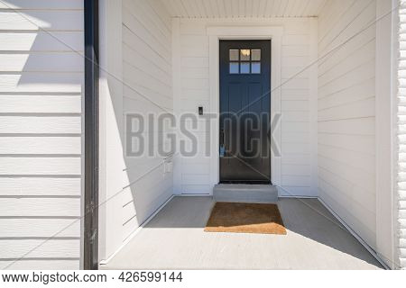 Exterior Of A House With A View Of Black Wooden Door With Glass Panel And An Enginered Wood Sidings