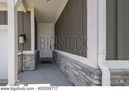 Front Door Corridor Exterior With Mocha Wooden Half Wall And Bricks