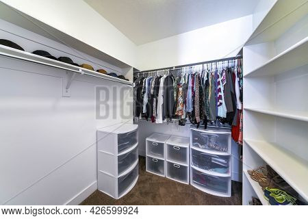 Walk-in Closet With Plastic Wardrobe Storage And Wall Mounted Shelves And Rods