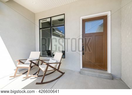 Front Porch With Two Rocking Chairs And Wooden Door With Glass Panel