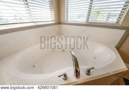 Corner Bathtub With Widespread Faucet Against The Two Windows