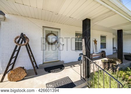Porch Exterior With Windows, White Bricks Wall And Dark Wood Posts