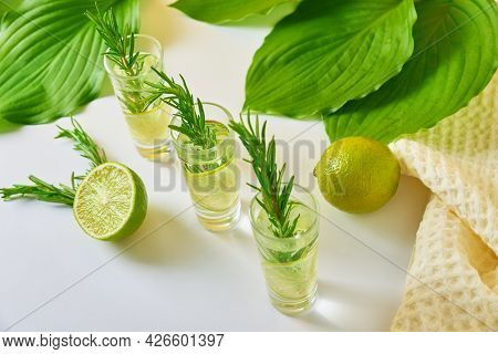 Summer Alcoholic Cocktail. Refreshment Lemon Soda Drink. Gin And Tonic With Lime And Rosemary On Tab