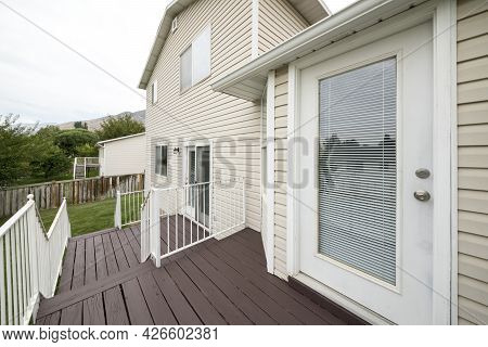 Exterior Of A House With Vinyl Wood Wall, Elevated Wooden Deck And Doors With Glass Panels