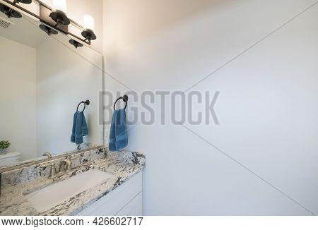 Vanity Sink Of A Bathroom With Marble Top And Black Metal Lights Fixture