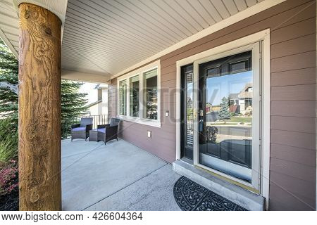 Front Porch Of A House With Engineered Wood Siding Wall And Log Column Post