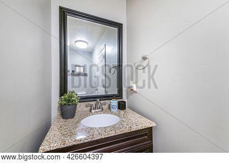 Single Vanity Sink With Framed Mirror And Granite Countertop