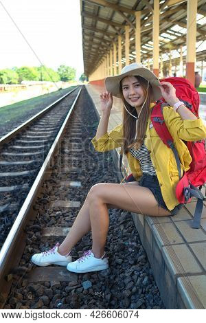 Asian Women Tourist With Backpack For Travel Sitting On Edge Of Train Railway, Journey Concept, Outd