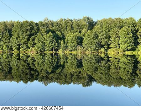Forest Reflects In Still Mirror-like Lake Water In Summer Day