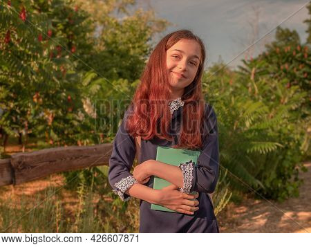 School Concept. Schoolgirl In A School Dress With A Notebook And A Backpack Outdoors.