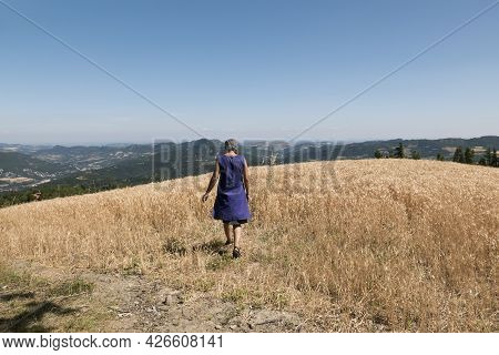 Mature Woman In A Barley Field Against Blue Sky
