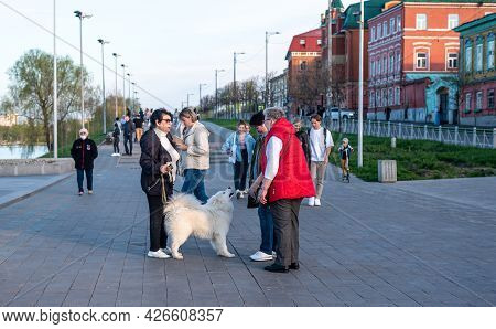 Kazan, Russia - May 08 2021: Positive Senior Women Friends In Jackets Walk With Cute Playful White L
