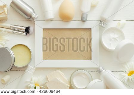 White Frame Set Cosmetic Products In White Packaging On Wooden Table With Flowers, Cosmetic Bag. Bea