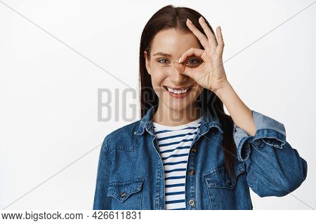 Zero Problems, Alright. Smiling Young Woman Shows Okay Ok Sign Near Eye And Looking Confident, Assur