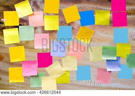 Multi-colored Empty Paper Note Sticky On Wooden Board For Write A Short Note For Reminder A To Do Li