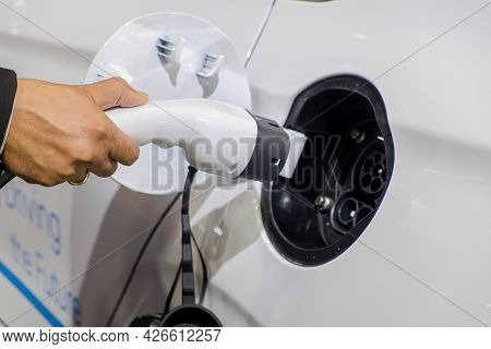 Close-up Hand Of Businessman Who Holding A Rechargeable Machine Plug For Charger Battery On Socket O